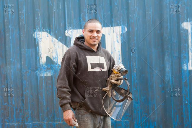 Welder holding welders mask smiling at camera