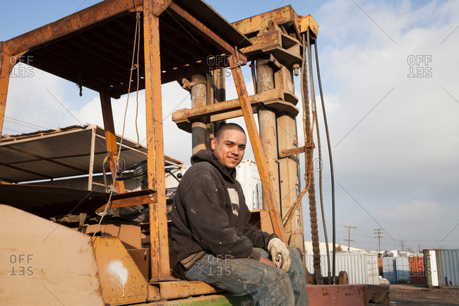 Man on construction site sitting on heavy machinery
