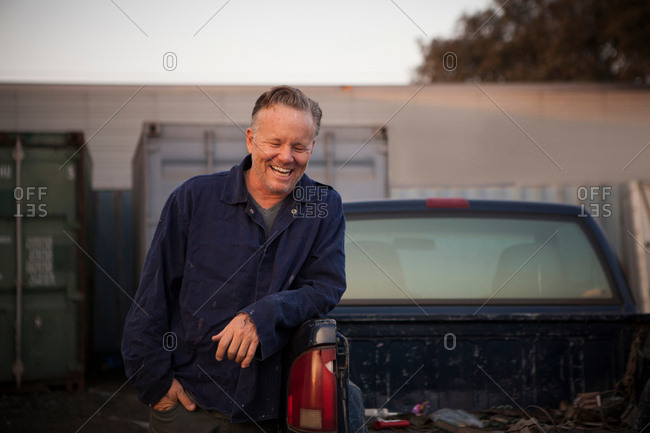 Man leaning against truck smiling