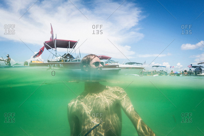 Split water level surface image of teenage boy in water, Crab Island, Emerald Coast, Gulf of Mexico, USA