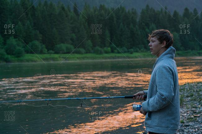 Teenage boy fishing in river at sunset, Washington, USA