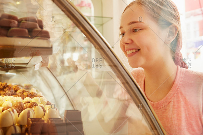 Girl in bakery looking at cakes in display cabinet smiling