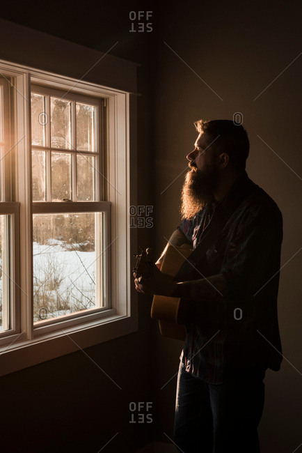 Man playing guitar beside window