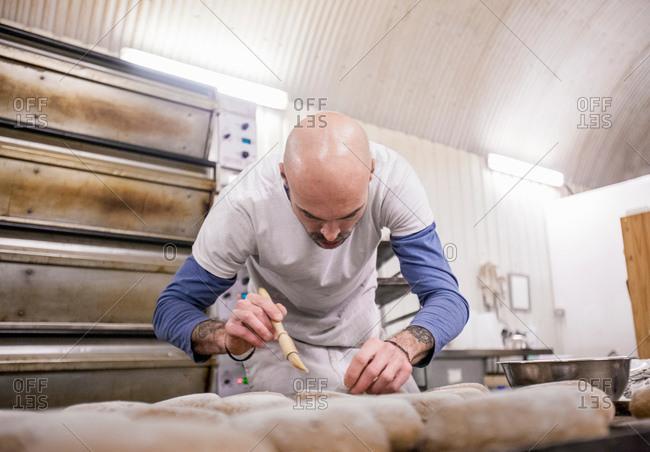 Baker brushing bread in bakery