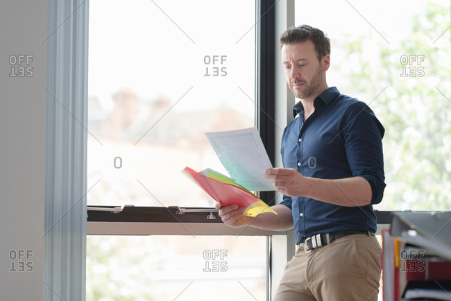 Man contemplating and reading papers by office window