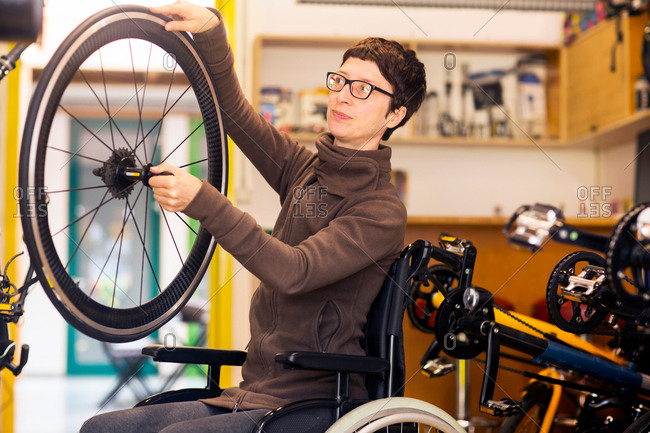 Woman in wheelchair in bicycle repair shop, holding bicycle wheel