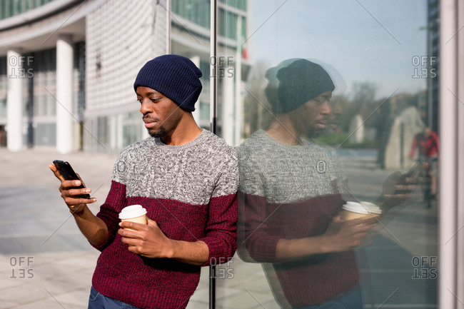 Young man, outdoors, leaning against window, using smartphone, holding disposable coffee cup
