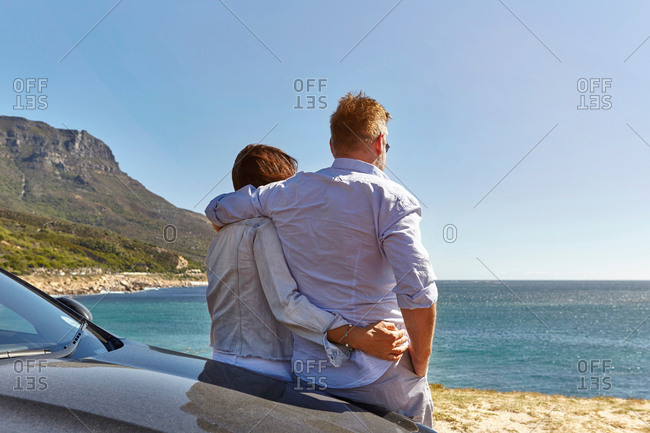Couple leaning on car bonnet, looking at coastal view, rear view, Cape town