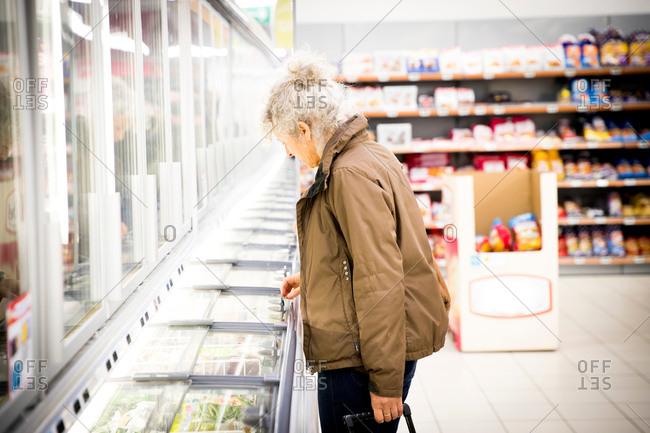 Mature woman in supermarket, looking in freezer cabinet