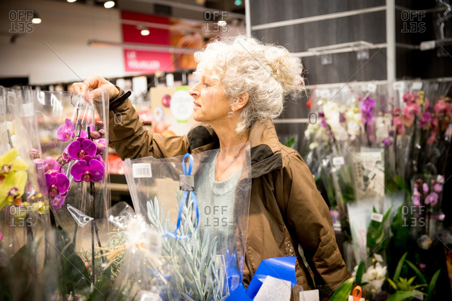 Mature woman in supermarket, looking at plants and flowers