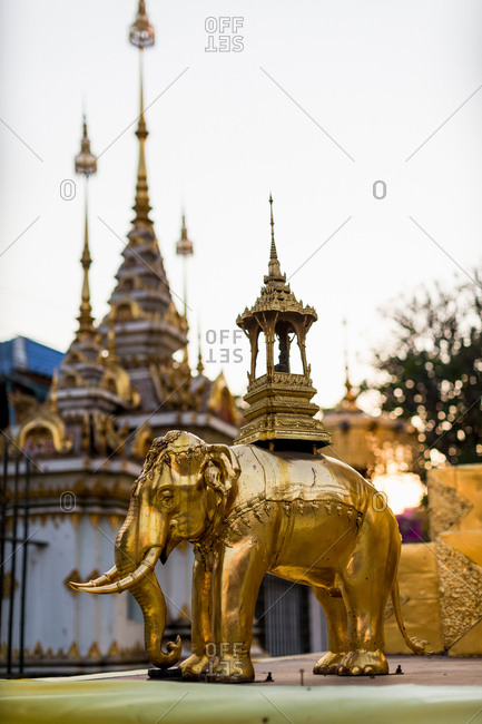 Golden elephant statue and spires of buddhist temple, Chiang Mai, Thailand