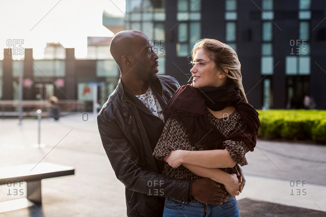 Young couple in city hugging and gazing at each other