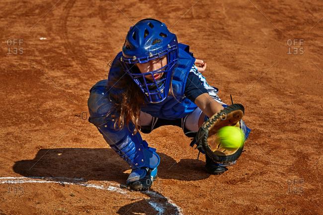 Teenage girl catching baseball