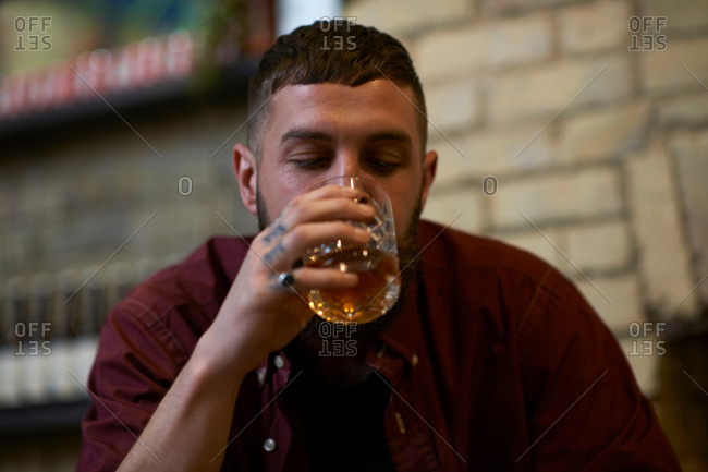 Young man with tattooed fingers drinking tumbler of spirit in public house