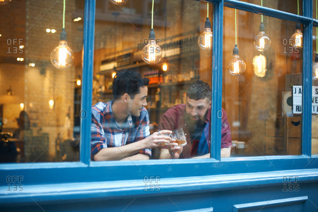 Window view of two men raising a glass in public house