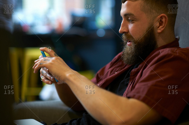 Young man looking at smartphone in public house
