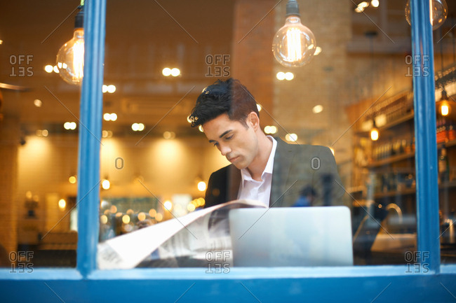 Window view of businessman reading broadsheet news in cafe