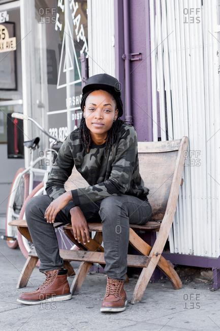 Portrait of cool female barber sitting on deckchair outside barber shop