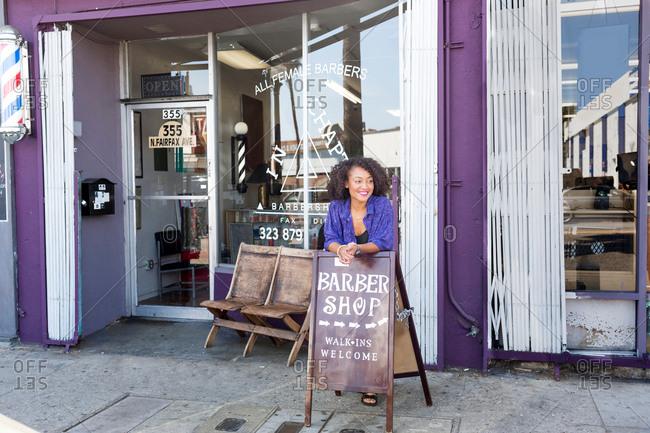 Female barber outside barber shop front