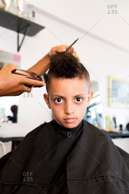 Female barber's hands using hair clippers on boy's hairstyle in barber shop