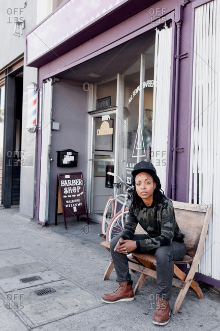 Portrait of cool female barber sitting on deckchair at barber shop front