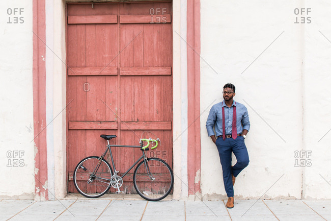 Young businessman cyclist leaning against wall waiting