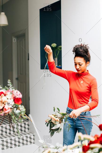 Female florist tying cut flowers in florists workshop