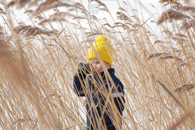 Boy standing in long grass, in snow covered landscape