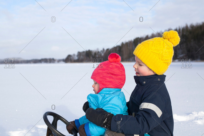 Two young brothers sitting on sledge, in snow covered landscape