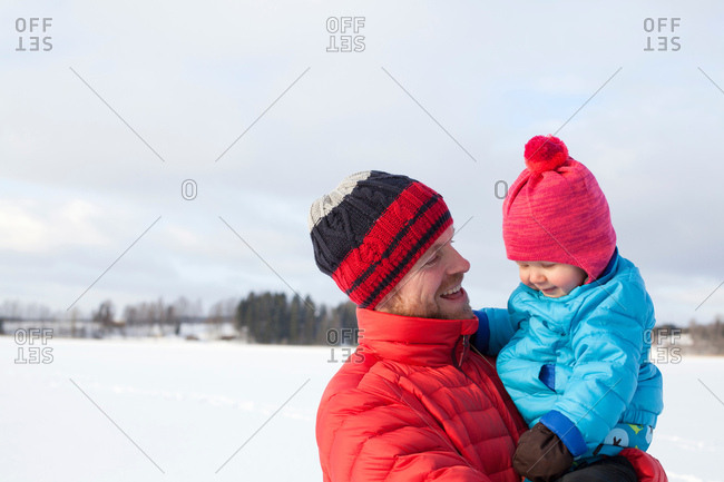 Father holding young son, in snow covered landscape