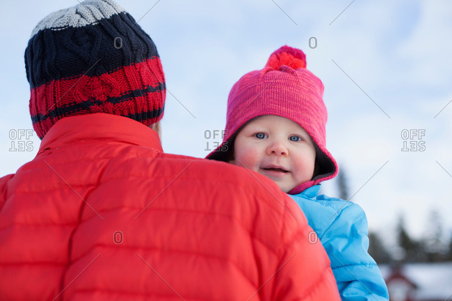 Father carrying young son in snow covered landscape