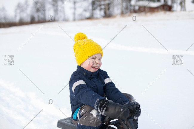 Young boy sitting on sledge, in snow covered landscape