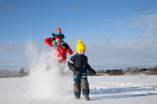 Father and two sons fooling around, running through snow covered landscape