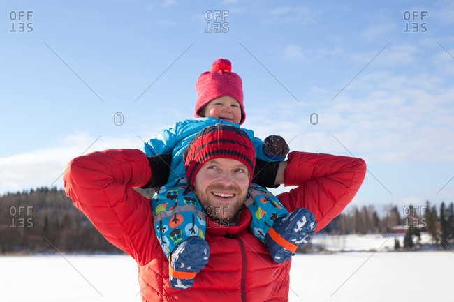 Father carrying young son on shoulders, in snow covered landscape