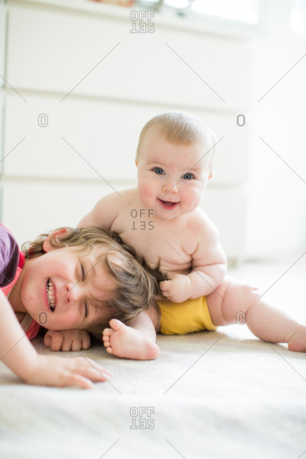 Young boy playing with baby sister, indoors