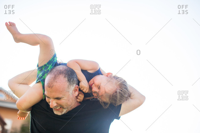 Father and son fooling around, outdoors, father carrying son over shoulders