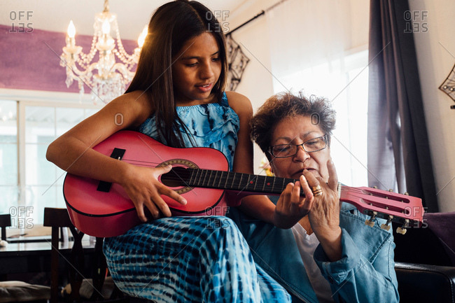Grandmother teaching granddaughter to play guitar