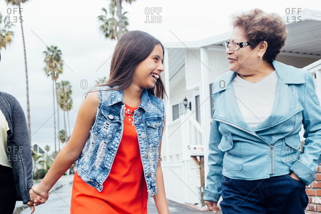 Grandmother and granddaughter walking in street