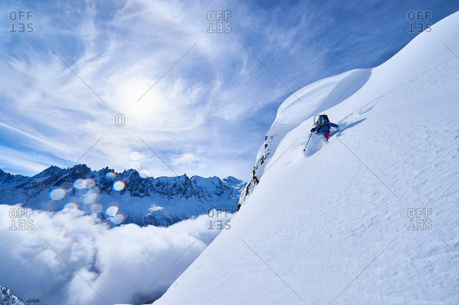 Woman skiing down steep mountainside in Swiss Alps, Gstaad, Switzerland