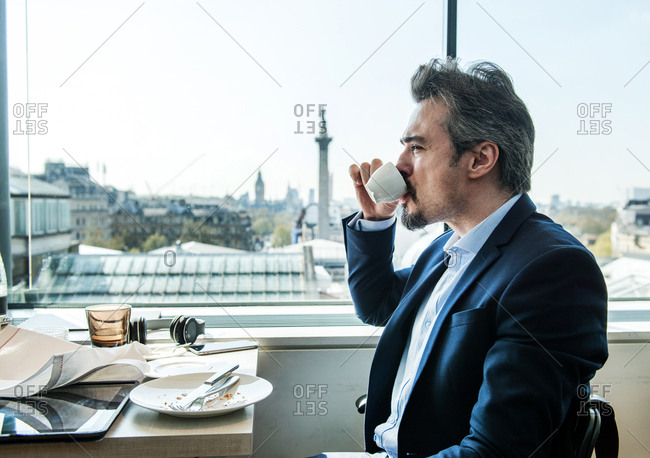 Businessman drinking coffee by restaurant window with rooftops views, London, UK