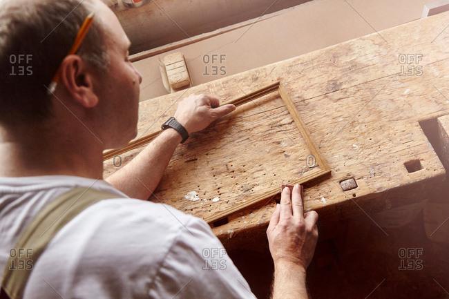 Over shoulder view of carpenter sanding picture frame at workbench