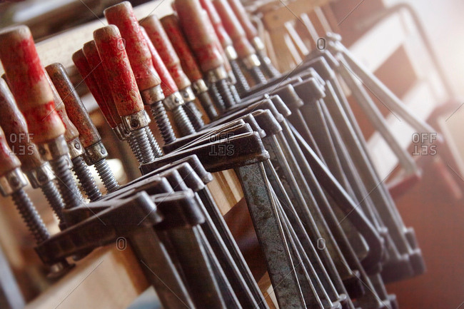 Row of carpenters clamps on workshop shelf