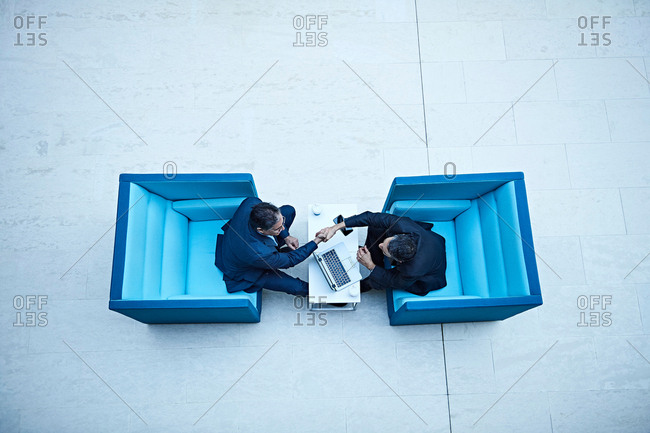 Overhead view of businessmen shaking hands in office atrium
