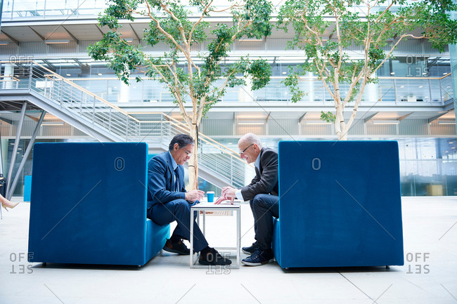 Two businessmen having discussion meeting in office atrium armchairs
