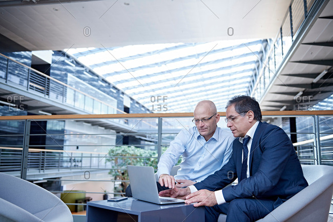 Two mature businessmen looking at laptop in meeting on office balcony