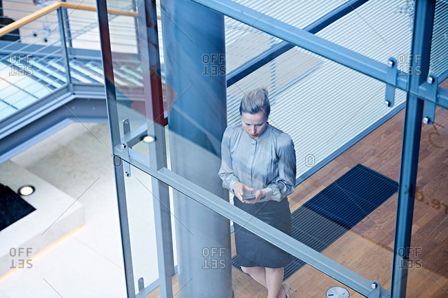 High angle view of businesswoman looking at smartphone on office stairway
