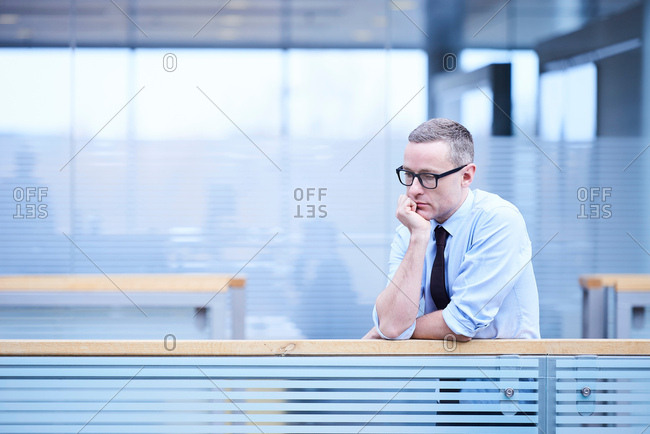 Stressed businessman with chin on hand in office atrium