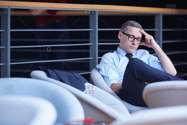 Businessman sitting reading on office balcony