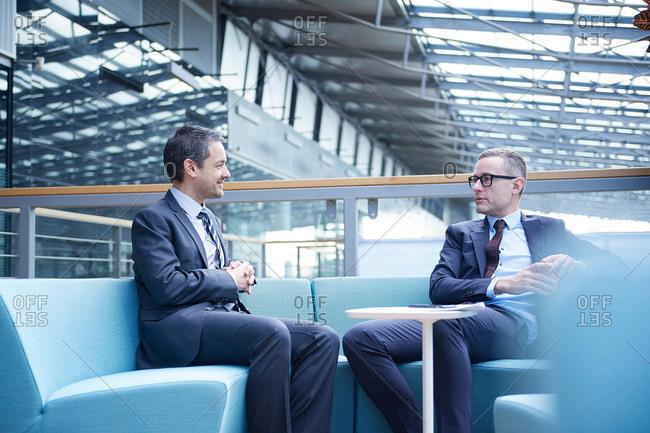 Businessmen meeting on sofa in office atrium
