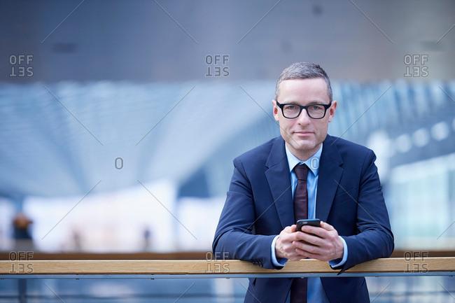 Portrait of businessman holding smartphone on office balcony
